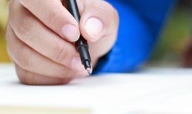 Kvinnlig hand med vårskjortahandstil något med pennan Fotografering för Bildbyråer