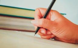 Kvinnlig hand med vårskjortahandstil något med pennan Arkivbild