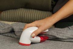 Kvinnlig hand och apparat för att ta dem bort Ta bort förbandsgas som pilling från tröjan arkivfoto