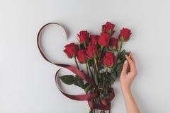 Kvinnlig hand och bukett av röda rosor med bandet för ferie för st-valentindag som isoleras på vit arkivfoto