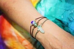Kvinnlig hand som bär naturliga stenpärlarmband arkivbild