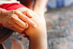 Kvinnlig hand som behandlar det tålmodiga knäet för ` s med myggan för myggatuggor royaltyfria foton