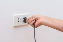 Kvinnlig hand som försöker till att plugga i anordning till elektriskt uttag Royaltyfria Bilder