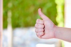 Kvinnlig hand som ger tummarna upp mot naturlig bakgrund Arkivfoton