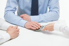 Kvinnlig hand som knuffar pengar under affärspartners hand Arkivbild