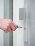 Kvinnlig hand som låser dörrlåset upp Arkivfoton