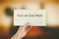Kvinnlig hand som levererar ett kuvert på suddig bakgrund Arkivfoto