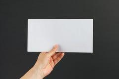 Kvinnlig hand som levererar ett vitt kuvert på svart bakgrund Arkivfoton