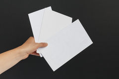 Kvinnlig hand som levererar 3 kuvert på svart bakgrund Royaltyfri Bild