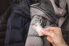 Kvinnlig hand som ner rymmer utfyllnadsgodsprövkopian för vinteromslag arkivbilder