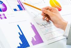 Kvinnlig hand som pekar blyertspennan på finansiella diagram fotografering för bildbyråer
