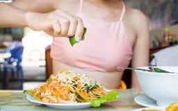 Kvinnlig hand som pressar limefrukt på grön papayasallad arkivfoton