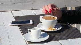 Kvinnlig hand som rör kaffe med en tesked i ett utomhus- kafé arkivfilmer