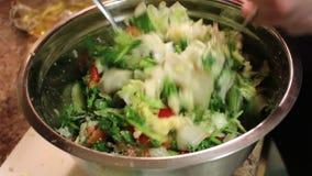 Kvinnlig hand som rör sallad för ny grönsak med ostfeta i köket Blandningen av grönsaker Närbild lager videofilmer