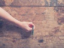 Kvinnlig hand som riting på skrivbordet arkivbild