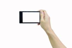 Kvinnlig hand som rymmer den moderna smarta telefonen med den vita skärmen på whit Royaltyfria Bilder