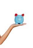 Kvinnlig hand som rymmer en blå moneybox Royaltyfri Fotografi