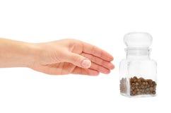 Kvinnlig hand som rymmer en genomskinlig glass krus av kryddan från pepparkornet Royaltyfri Bild