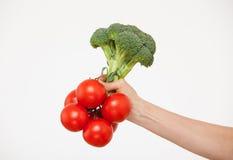 Kvinnlig hand som rymmer en grupp av tomater, broccoli arkivbild