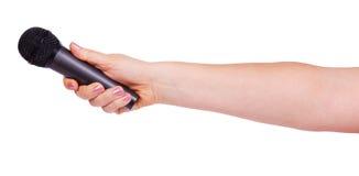 Kvinnlig hand som rymmer en mikrofon Arkivbild