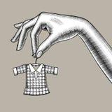 Kvinnlig hand som rymmer en mycket liten liten klänning på hängare stock illustrationer