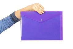 Kvinnlig hand som rymmer en purpurfärgad plast- mapp arkivfoto