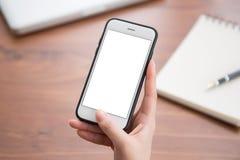 Kvinnlig hand som rymmer en vit telefon med skärmen på a Royaltyfri Fotografi