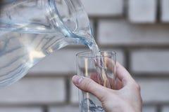 Kvinnlig hand som rymmer ett exponeringsglas, hällande vatten ut ur en kanna Royaltyfri Foto