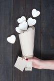 Kvinnlig hand som rymmer facket med vita kaka-hjärtor royaltyfria foton