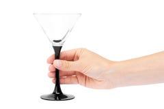 Kvinnlig hand som rymmer tomt vinexponeringsglas bakgrund isolerad white Arkivfoto