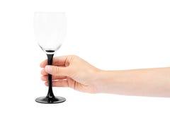 Kvinnlig hand som rymmer tomt vinexponeringsglas bakgrund isolerad white Arkivfoton