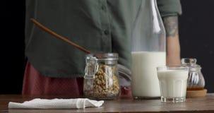 Kvinnlig hand som sätter exponeringsglas av granola stock video