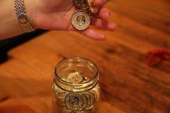 Kvinnlig hand som sätter myntet in i kruset Royaltyfria Bilder