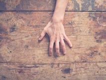 Kvinnlig hand som skrapar trätabellen royaltyfria foton