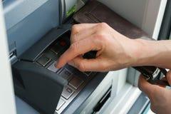 Kvinnlig hand som skriver in en säker STIFTkod på en kontant punkt eller ATM upp slut och i detalj royaltyfri fotografi