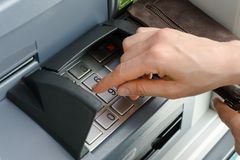 Kvinnlig hand som skriver in en säker STIFTkod på en kontant punkt eller ATM upp slut och i detalj arkivfoto