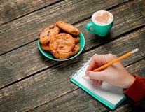 Kvinnlig hand som skriver något i anmärkning nära kakan royaltyfria bilder