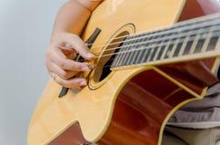 Kvinnlig hand som spelar musik vid den akustiska gitarren Royaltyfria Bilder