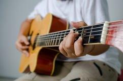 Kvinnlig hand som spelar musik vid den nära akustiska gitarren - sköt upp och Arkivbild