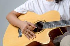 Kvinnlig hand som spelar musik vid den nära akustiska gitarren - sköt upp och Royaltyfri Foto