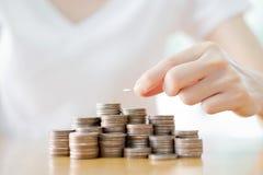 Kvinnlig hand som staplar guld- mynt Arkivfoto
