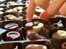 Kvinnlig hand som upp väljer choklader Royaltyfri Foto
