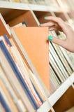 Kvinnlig hand som väljer en höger bok arkivbild