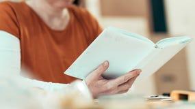 Kvinnlig handbok för anvisning för projekt för snickareläsning DIY royaltyfri bild