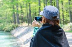 Kvinnlig handelsresande med den smarta telefonen som tar ett foto på kamikochien nagano Japan arkivfoto