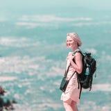 Kvinnlig handelsresande med en ryggsäck på henne som tycker om tillbaka sikterna från bergen av Montserrat i Spanien Royaltyfri Fotografi