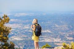 Kvinnlig handelsresande med en ryggsäck på henne som tycker om tillbaka sikterna från bergen av Montserrat i Spanien Royaltyfri Bild