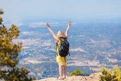 Kvinnlig handelsresande med en ryggsäck på henne som tycker om tillbaka sikterna från bergen av Montserrat i Spanien Royaltyfria Bilder