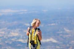 Kvinnlig handelsresande med en ryggsäck på henne som tycker om tillbaka sikterna från bergen av Montserrat i Spanien Royaltyfria Foton