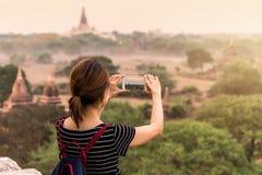 Kvinnlig handelsresande som fotograferar den forntida pagoden på Bagan Royaltyfria Bilder
